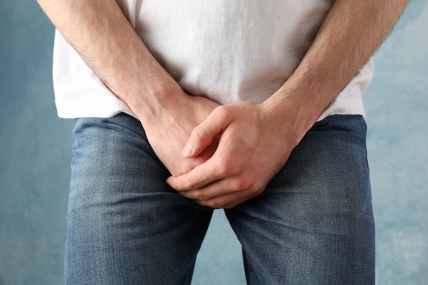 man-holds-his-crotch-blue-close-up